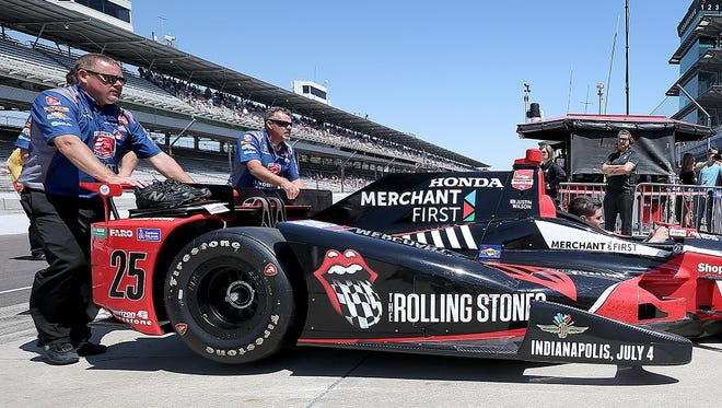 Crew members push the new-look Rolling Stones car of Justin Wilson after Carb Day practice Friday at Indianapolis Motor Speedway.