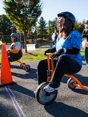 Brandi Simmons laughs as she prepares to begin her leg of a tricycle relay race as part of a fundraiser for Community Child Care in Staunton on Saturday, Oct. 17, 2015.