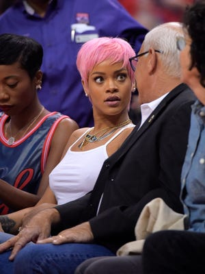 Singer Rihanna, center, and Steve Soboroff, right, president of the L.A. Police Commission, watch the Los Angeles Clippers play the Oklahoma City Thunder in the second half of Game 6 of the Western Conference semifinal NBA basketball playoff series, Thursday, May 15, 2014, in Los Angeles. The Thunder won 104-98, taking the series 4-2.  (AP Photo/Mark J. Terrill)   ORG XMIT: NYOTK