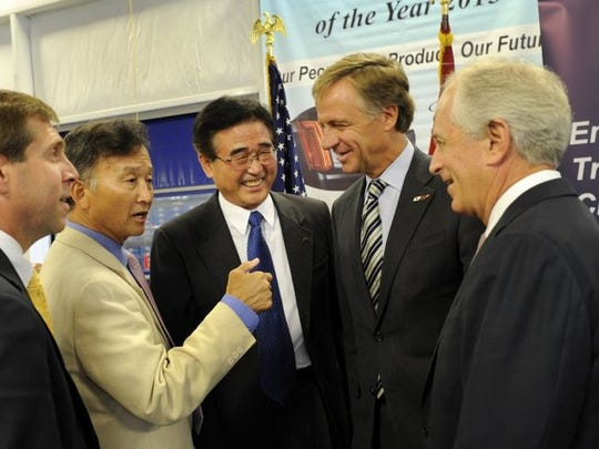 Dr. Tom Kim, second from left, jokes with Y.K. Woo, president of SL America, Gov. Bill Haslam, Sen. Bob Corker and U.S. Rep. Chuck Fleischmann, far left, after an announcement of an $80.5 million investment and creation of 1,000 jobs in Anderson County at the SL Tennessee plant on July 25, 2014.