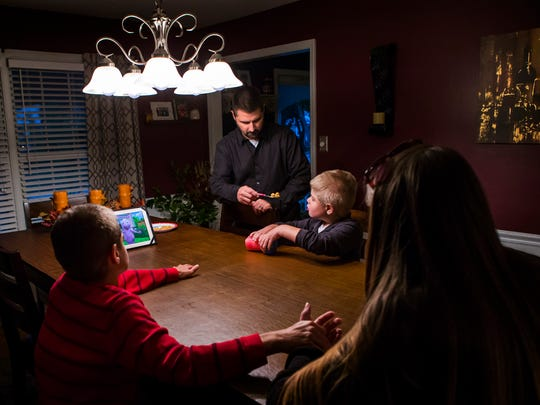 Carl Kapes feeds his eight year-old son Brayden dinner while Brayden watches the Backyardigans on a iPad at their dinner table at the Kapes home in Wilmington on Wednesday afternoon, October 26, 2016. Sharon Rapposelli, a home health aid for the Kapes family, tries to comfort eleven year-old Ryan as he suffers through discomfort caused by constipation across from Brayden and Carl.