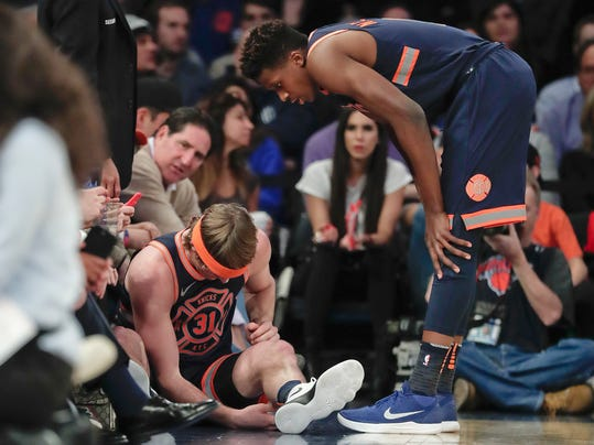 New York Knicks guard Ron Baker (31) sits on the sideline with an injury to his right arm as guard Frank Ntilikina (11) looks on during the first quarter of an NBA basketball game against the Brooklyn Nets, Tuesday, Jan. 30, 2018, in New York. (AP Photo/Julie Jacobson)