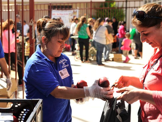 Volunteer Araceli Ruiz distributes fresh apples as