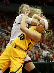 Louisville's Kylee Shook, left, is fouled by Marquette's Isabelle Spingola during first half action. March 18, 2018