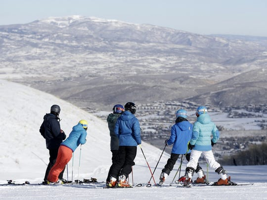 Skiers stand atop a hill at Utah's Park City Mountain Resort.