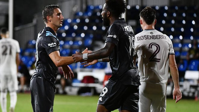 Minnesota United midfielder Ethan Finlay (13) celebrates his goal with defender Romain Metanire (19) during the first half against the Colorado Rapids at ESPN Wide World of Sports in Kissimmee, Fla., on July 22, 2020.
