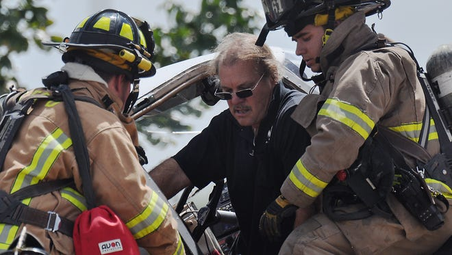 Firefighters rescue a man inside a small aircraft that crashed onto a parking lot near Deleon Street and Colonial Boulevard in Fort Myers Monday afternoon.