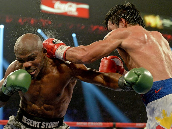 Timothy Bradley Jr. (brown gloves) and Manny Pacquiao (red gloves) during their WBO World Welterweight Championship fight at MGM Grand Garden Arena. Manny Pacquiao won by decision.