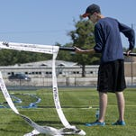 Wendell Alderdyce, of Port Huron, sets up courts for the upcoming Volleygrass Tournament Thursday at Port Huron Northern High School.