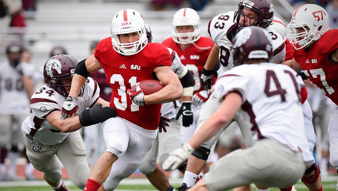 St. John's Sam Sura is bought down by Augsburg's Matt Shively after a gain in the first half.