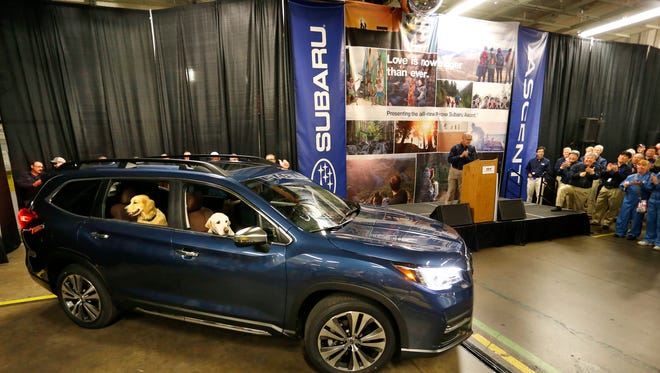 Stevie and Luther peer out the windows at associates gathered as the first new Subaru Ascent rolls off the assembly line Monday, May 7, 2018, at Subaru of Indiana Automotive, Inc. The three-row SUV can seat up to eight passengers. The two dogs have appeared in several Subaru commercials.