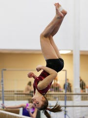 McCutcheon gymnast Emma Taylor practices her dismount from the balance beam Wednesday, January 18, 2017, at Elite Gymnastics, 3822 Fortune Drive in Lafayette. Taylor is a sophomore.
