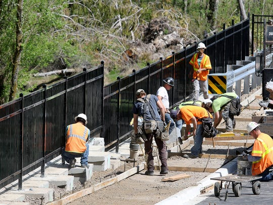 FILE PHOTO – Redside Construction workers and landscape contractors work on the new West Kingston Road Bridge in April 2018.