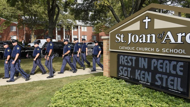 Michigan State Police officers arrive for the funeral for Detroit Police Sgt. Kenneth Steil on September 23, 2016.