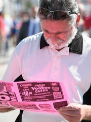 Mark Smith doing some lunch time planning as the lunch time crowd fills West Franklin Street for the Evansville West Side Nut Club Fall Festival Thursday, October 6, 2016