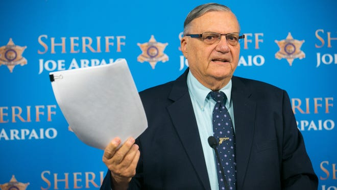 Maricopa County Sheriff Joe Arpaio holds up photos of dogs found dead at a Gilbert kennel during a June 2014 press conference.