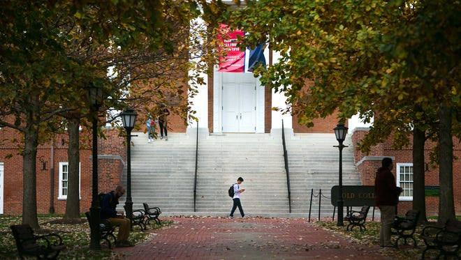 Students hang around Old College near Main Street on the UD campus.