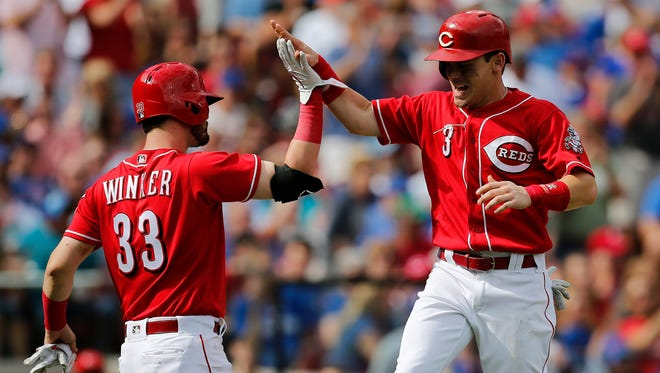 Cincinnati Reds second baseman Scooter Gennett (3) high fives with right fielder Jesse Winker (33) as he crosses the plate on a RBI single by third baseman Eugenio Suarez (7) in the third inning of the MLB National League game between the Cincinnati Reds and the Chicago Cubs at Great American Ball Park in downtown Cincinnati on Saturday, June 23, 2018. The Reds led 8-1 after three innings.