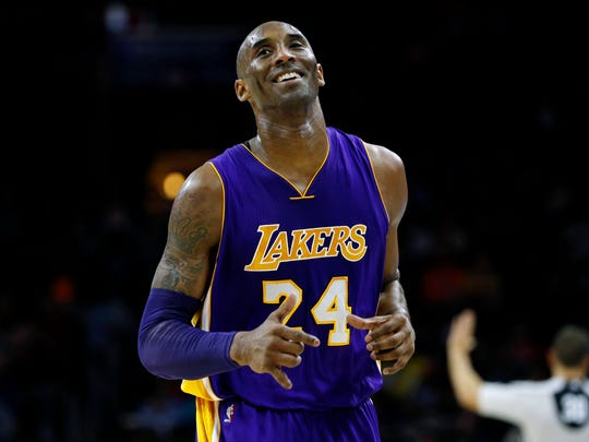 Los Angeles Lakers' Kobe Bryant smiles as he jogs to the bench during the first half of an NBA basketball game against the Philadelphia 76ers, Tuesday, Dec. 1, 2015, in Philadelphia.