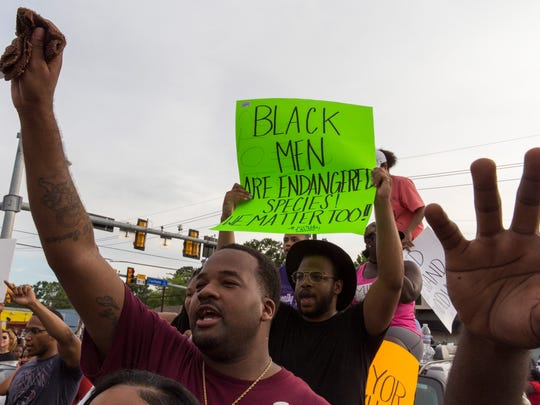 Aaron Taplin and other protesters raise their arms during a vigil for Alton Sterling, at the convenience store where the 37-year-old was shot dead while being taken into police custody, in Baton Rouge, La. July 6, 2016.