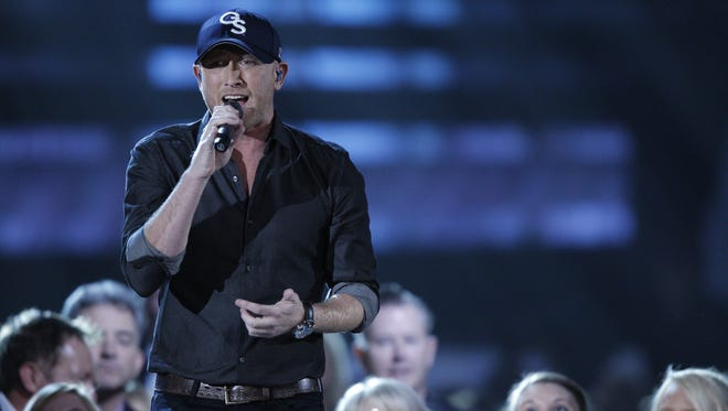 Cole Swindell performs in the audience at the 48th annual CMA Awards at the Bridgestone Arena on Wednesday, Nov. 5, 2014, in Nashville, Tenn.