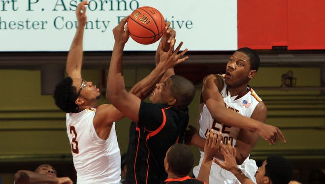 Mount Vernon's Yhanni Bartley, left, and Judah Alexander, right, block the path of Spring Valley's Kai Mitchell as he goes up for a shot during the Class AA championship game March 2, 2014, at the Westchester County Center in White Plains.