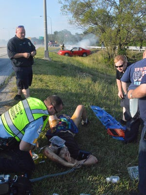 A man receives medical attention after being removed from his burning car following a crash along Del. 141 on Sunday.