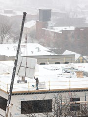 Construction crews work atop the building at College