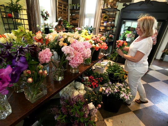 Mary Walker picks flowers to make a Mother's Day arrangement at Robin Wood Flowers on Dana Road in Evanston Thursday. The local company is expected to make about 400 arrangements for Mother's Day.