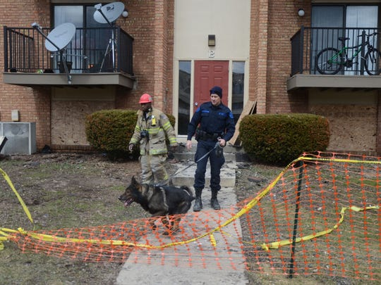 Battle Creek Fire Department Inspector Lt. Quincy Jones, left, and Michigan State Police Trooper Joel Service and his accelerant-sniffing dog Ki leave the Arbors after an inspection Thursday.