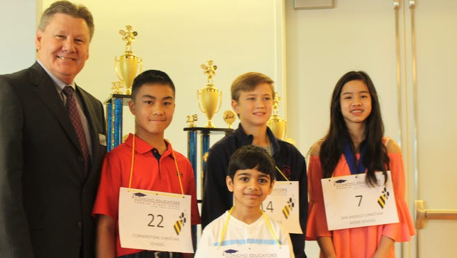 Winners of the 30th annual San Angelo Spelling Bee pose before their trophies. From left to right: Jerry Merrill, of Concho Educators Federal Credit Union; Kasey Torres, first place; Davis Bailey and Akash Vukoti, second place; and Franchesca Untalan, third place.