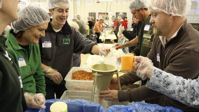 """Volunteers Vicki Koppenhafer of Evendale, Josh Reddington of Mason, and Brad Grimm of Liberty Township work together to make """"Hands Against Hunger"""" meals for people in Haiti and sub-saharan Africa at A Child's Hope International's Hope Factory in Sharonville as part of Make A Difference Day 2013."""