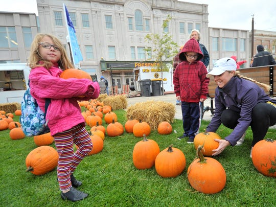 Falynn Bodenheimer, 6, left, poses for a photo while her 5-year-old brother Reid and mother Keri Anne Steger, select pumpkins during Harvest Fest at the 400 Block in downtown Wausau.