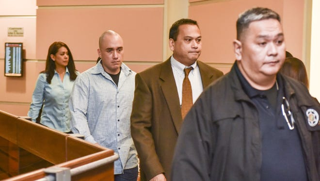 Guam Police Officer Mark Torre Jr., second from left, enters the courtroom for his arraignment hearing at the Guam Judicial Center in Hagatna on Wednesday, July 29. Torre, who faces allegations of murder, manslaughter and aggravated assault in the July 13 shooting death of fellow officer Sgt. Bert Piolo, pleaded not guilty to the charges during the hearing.