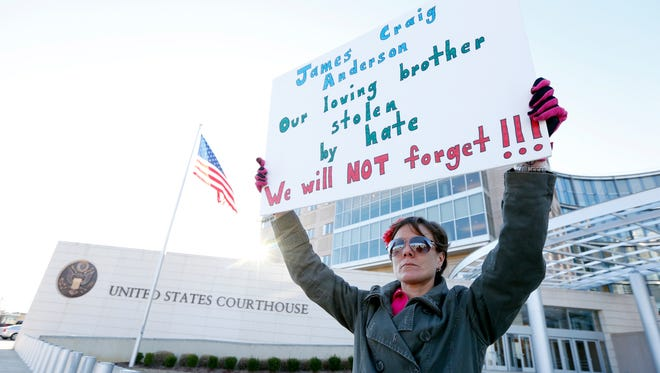 Amelie Hahn, braves cold weather as she holds a poster memorializing the 2011 rundown death of James Craig Anderson in front of the federal courthouse in Jackson, Miss., Wednesday, Jan. 7, 2015. Two of the men charged in the series of 2011 racial beatings that resulted in Anderson's death were expected at a change-of-plea hearing.
