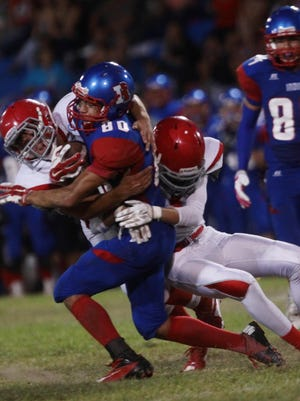 From Left, Desert Mirage High School defenders Jaime Serrano and Dylan Arreola take down Indio High School's Brian Cervantes at Ed White Stadium in Indio on August 28, 2015.