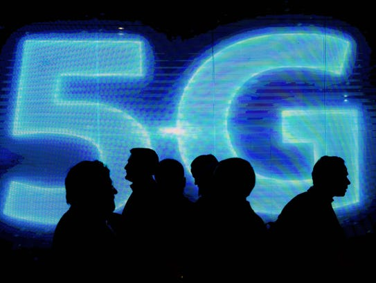 Visitors walk past a 5G logo during Mobile World Congress