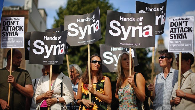 Anti-war protesters gather on College Green outside the Houses of Parliament  Aug. 29 in London. Prime Minister David Cameron has recalled Parliament to debate the U.K.'s response to a suspected chemical weapons attack in Syria.