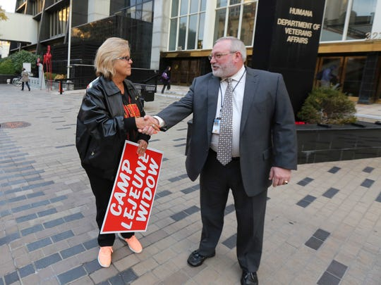 Bob Clay, with the VA office, greets Tara Craver, a Marine widow from Florida, as she protests outside of the office of the Department of Veterans Affairs on Thursday morning.  Clay invited Cravers inside to talk.  Cravers husband, Karle Craver, died of esophageal cancer two years ago, and she is fighting the VA because she believes her husband was among the Lejeune veterans and family members who contracted diseases as the result of exposure to contaminated water at the North Carolina Marine base. Because Craver is seeking benefits as the result of Lejeune exposure, her claims fall under the purview of the VA's Louisville Claims Center, which is handling those cases.December 1, 2016