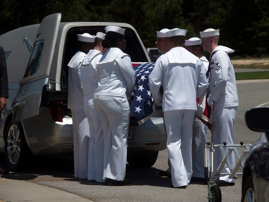 The remains of John Schoonover, a sailor killed on the USS Oklahoma during the Japanese attack on Pearl Harbor, are removed from a hearse by a Navy Honor guard at Barrancas National Cemetery on Tuesday.