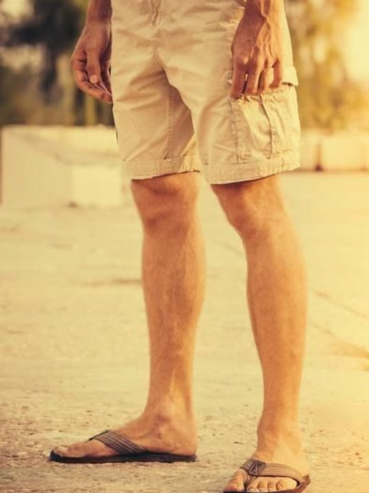 Man Feet wearing shorts and flip flops standing Outdoor summer