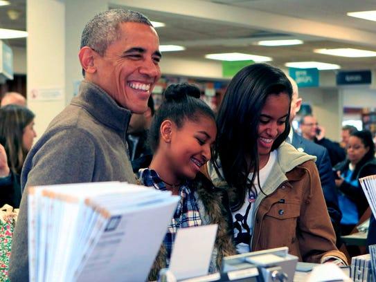 President Obama and daughters Sasha (c) and Malia purchase
