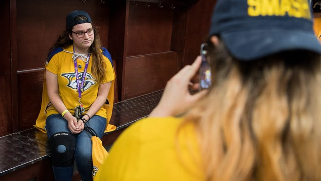 Kristina Campbell, left, has her picture taken in the Predators' locker room by her sister, Kelly Campbell, during the Predators Draft Party at Bridgestone Arena in Nashville, Tenn., Friday, June 23, 2017.