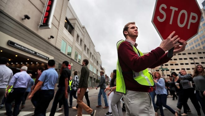 Drew Blake directs fellow ServiceMaster employees to cross Second Street during an emergency drill at the company's new headquarters Monday, Feb. 19, 2018. The first 180 employees moved into ServiceMaster's downtown headquarters, where they set up their work stations and took part in a safety briefing before being addressed by company executives.