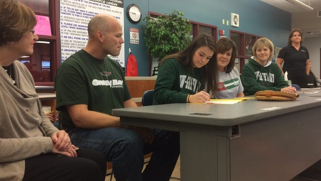 Pulaski senior Liz Pautz signs a national letter of intent with the University of Wisconsin-Green Bay softball team Wednesday at Pulaski High School with family members looking on.