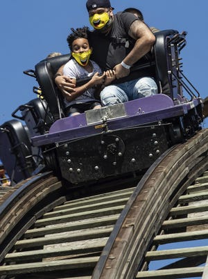 A man and child wearing face masks with cartoon smiles ride the wooden roller coaster at Playland amusement park at the Pacific National Exhibition, in Vancouver, on Sunday, Aug. 9, 2020. The roller coaster and other rides are operating at a reduced capacity due to COVID-19. Guests are required to wear face masks or coverings while waiting in lines and while on rides and the park is closed for an hour each afternoon for sanitization.