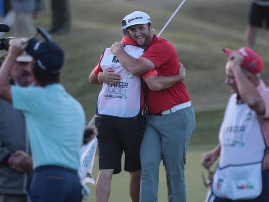 Jon Rahm hugs his caddy Adam Hayes after winning the