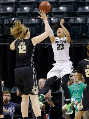 Michigan State forward Aerial Powers (23) makes a pass over Purdue center Nora Kiesler (12) in the second half of an NCAA college basketball game at the Big Ten Conference tournament in Indianapolis, Friday, March 4, 2016. Michigan State defeated Purdue 65-64. (AP Photo/Michael Conroy)