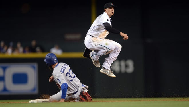 July 15, 2016; Phoenix; Arizona Diamondbacks shortstop Nick Ahmed (13) jumps over Los Angeles Dodgers base runner Scott Van Slyke (33) while turning a double play during the fifth inning at Chase Field in Phoenix.