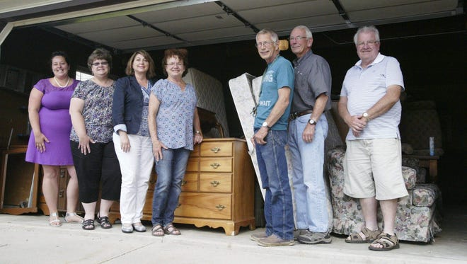 Members of a furniture ministry started in response to needs identified by Love INC store their first batch of furniture in a church garage prior to distributing it. Pictured, from left, is Katie Popp, executive director of Love INC of Sheboygan County; Lori Kramer, secretary of St. Peter's Episcopal Church of Sheboygan Falls; Mickey Heinig, church ministry coordinator for Love INC and member of St Peter's Episcopal Church Sheboygan Falls; Louise Robson, gap furniture ministry coordinator and member of St. Peter's Episcopal Church Sheboygan Falls; Dale Robson, gap furniture ministry coordinator and member of St. Peter's Episcopal Church Sheboygan Falls; Gary Kolste, church ministry coordinator for Love INC and member of Hingham Reformed Church; and Lloyd TerMaat, Love INC volunteer and member of First Reformed Church in Cedar Grove, who also coordinates an existing furniture ministry in inner-city Milwaukee.